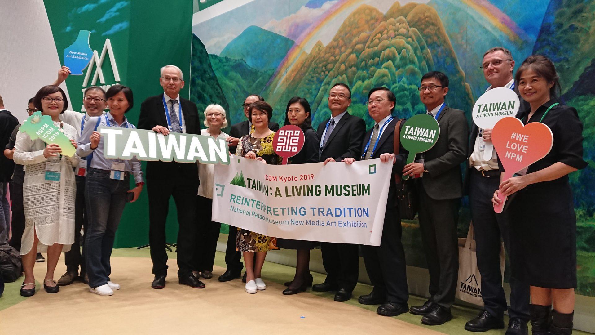 台灣館開幕儀式,理事長蕭宗煌(右5)及國際貴賓一起合影。背景為藝術家林惺嶽的畫作。(田偲妤攝影)