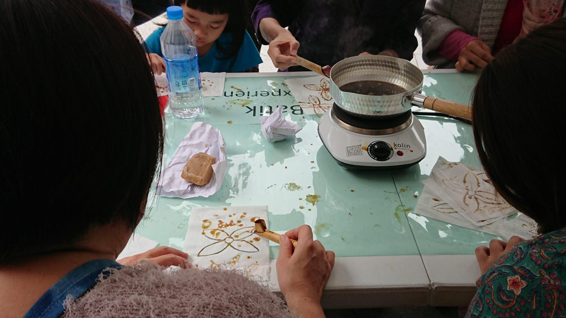 蠟染技藝體驗,用蠟染筆裝取鍋裡的蠟液,蠟液會從筆的尖端流出,可描繪於布面上。 (攝影:田偲妤)